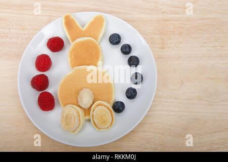 pancakes in a bunny rabbit pattern, banana for tail and feet, fresh raspberries and blueberries on the plate on a light wood table with copy space - Stock Photo