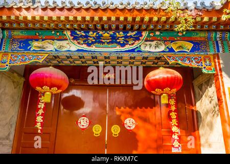 Ornate Red Door Lanterns New Year Sayings Yuer Hutong Neighborhood Beijing China. Yuer Hutong goes back to 1600s. The Chinese characters on the door - Stock Photo