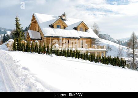 Traditional wooden mountain house built from wood logs on winter sunny day, Pieniny Mountains, Jaworki, Poland - typical farmhouse for this mountainou - Stock Photo