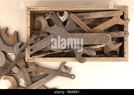 Collection of old rusty wrenches on a dirty floor. - Stock Photo