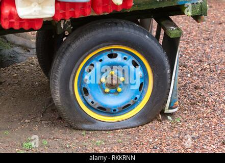 Flat rear tire on a colorful truck. - Stock Photo