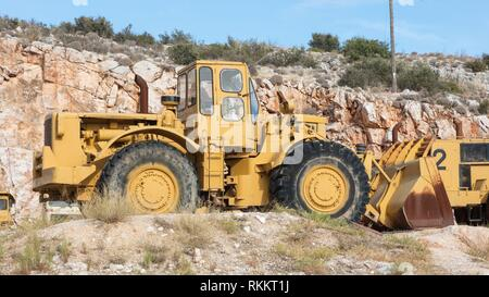 Old industrial bulldozer for stone waiting on a site in Greece. - Stock Photo
