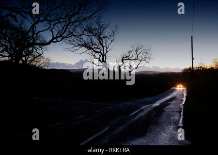Car driving fast along country road at dusk, night, on wet road, after rain storm, headlights on, bright, slippery road conditions, rural driving. - Stock Photo