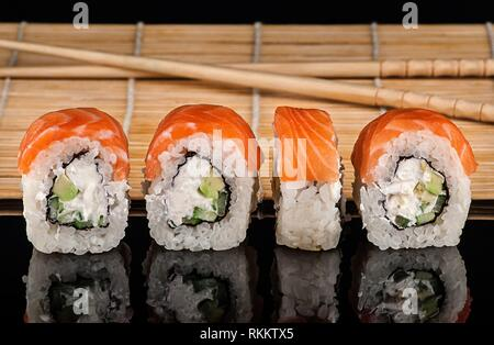 Several Philadelphia Sushi roll in a row. Sushi mat and sticks on a blurry background. Reflection. - Stock Photo