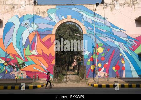 A girl walks past a street mural of a Oriental Pied Hornbill by Renato Reno in Lodhi Colony, New Delhi, India - Stock Photo