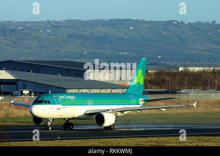 An Aer Lingus Airbus A320 prepares to take off from Belfast City Airport, Northern Ireland. The Airbus A320 family consists of short- to medium-range, narrow-body, commercial passenger twin-engine jet airlinersmanufactured by Airbus. The family includes the A318, A319, A320 and A321, as well as the ACJ business jet. The A320s are also named A320ceo (current engine option) after the introduction of the A320neo (new engine option) Final assembly of the family takes place in Toulouse, France, and Hamburg, Germany. A plant in Tianjin, China, has also been producing aircraft for Chinese airlines - Stock Photo