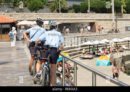 Two policewomen of Cascais, are patrolling seaside promenade  on bicycles. People are sunburning on the city  public beach on the Atlantic shore. - Stock Photo