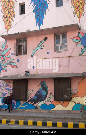 A man walks past a mural by Brazilian artists Bicicleta Sem Freio, in Lodhi Colony, New Delhi, India - Stock Photo