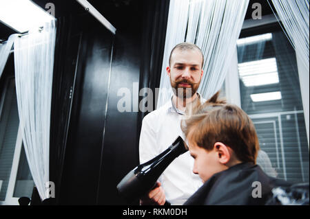 Cute little boy is getting haircut by hairdresser - Stock Photo