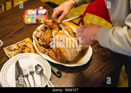 A man cuts up turkey using a large fork and knife. - Stock Photo