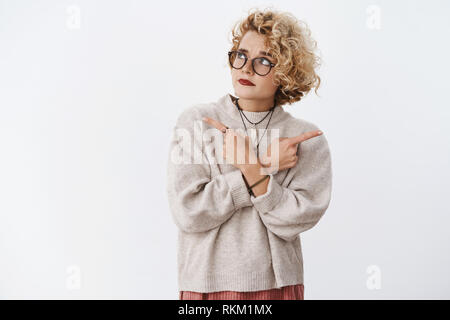 Unsure and hesitant cute questioned hipster female wearing glasses and makeup raising eyebrow doubtful looking suspicious and uncertain at upper left - Stock Photo