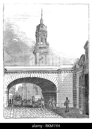 The clock tower, built in 1706, of St Magnus the Martyr on Lower Thames Street seen through an arch of the new London Bridge opened in 1831 from a design by John Rennie. - Stock Photo