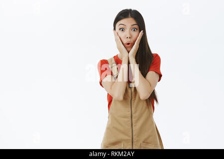 Girl receiving awesome news being surprised and amazed. Emotive young and cute and gentle asian woman gasping from amazement holding palms on cheeks - Stock Photo