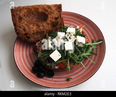large plate of sandwich with black rustic bread, feta, olives, rucola and tomatoes - Stock Photo
