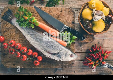 Shi drum fish (Umbrina cirrosa) on old wooden board with carrot, cherry tomatoes, black tomatoes, lemon, garlic, parsley and chili peppers, top view - Stock Photo