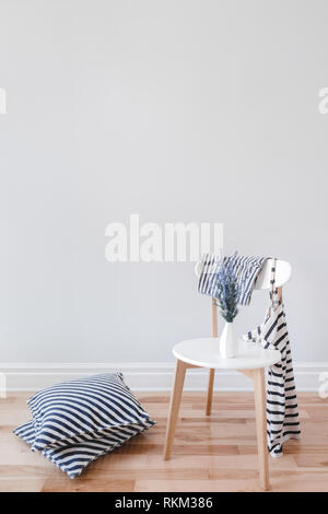 Modern interior with stylish chair, lavender flowers, striped cushions and clothes, on gray wall background with copy space. - Stock Photo