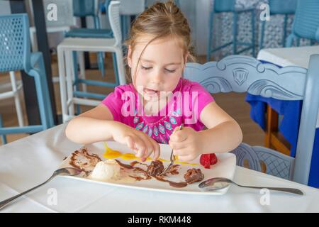 funny cute four years old blonde girl eating, and sticking out tongue, with spoon sweet dessert: black chocolate, vanilla ice cream, strawberries and - Stock Photo