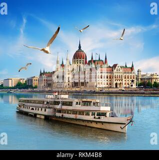 Seagulls over boat near Parliament on Danube river in Budapest. - Stock Photo