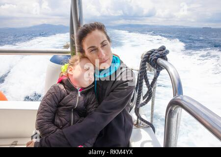 woman hugging her daughter sleeping, four years old girl, sitting on the stern of motor boat sailing in Strait of Gibraltar. - Stock Photo