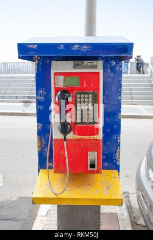 old and dirty public telephone on a street of Tarifa city, in Cadiz, Spain, Europe. - Stock Photo