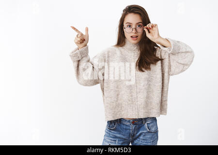 Questioned and impressed cute young 20s woman taking off glasses intrigued as pointing at upper left corner being curious with product asking question - Stock Photo