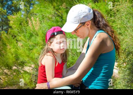 little girl four years old with sad face expression sitting on the legs of a woman, with caps, in the forest of the countryside. - Stock Photo