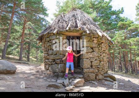 mountaineer little child, five years old girl, with trekking stick standing in door frame of ancient stone hut in Canencia forest (Madrid, Spain, - Stock Photo