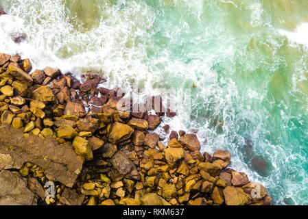 Top aerial view of blue waves crashing on rocky Australian coastline. Summer seascape with birds eye view shot over ocean waves and cliffs. Travel - Stock Photo