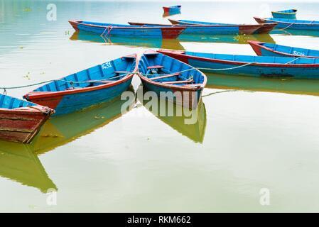 Pokhara, Nepal: Colourful boats on Phewa lake in Pokhara, the most popular and visited lake of Nepal. - Stock Photo