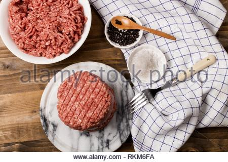 fresh raw northern ireland beef burger patty with reduced fat on marble. - Stock Photo
