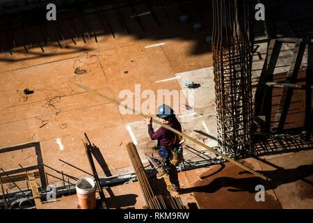 A construction worker carries steel bars at Vancouver House, a tower under construction in Vancouver, BC, Canada. - Stock Photo