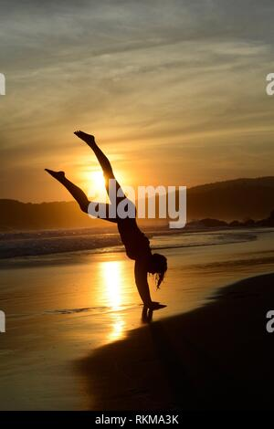 Woman, 26, doing a handstand on the beach at sunset near San Agustinillo, Oaxaca, Mexico. - Stock Photo