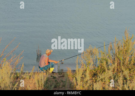 Kazan, Russia - Aug 10, 2018: Fisherman on river bank - Stock Photo