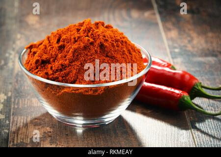 Composition with bowl of chili powder on wooden table. - Stock Photo