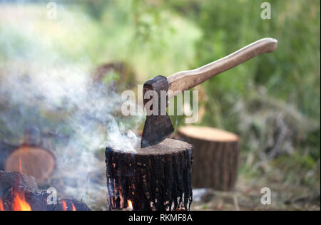 Axe in tree stump and campfire with smoke in summer forest at sunny day - Stock Photo
