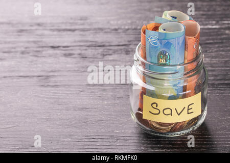 Euro notes and coins in a glass jar on a black wooden table with shiny reflection on a glossy surface. Money saving concept