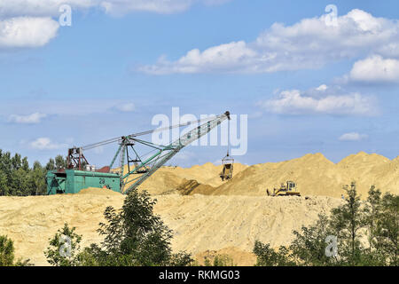 Bagger operation in a small surface mine - Stock Photo