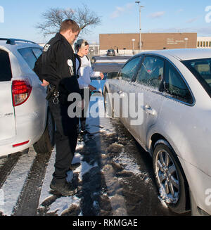 Emporia, Kansas USA, February 17, 2015 5:14pm Officer Shcuman is waved down by Payton Weiss in the parking lot near the HPER building. Peyton a senior  from Russel, Kansas states that she can not get into to her car as the key will not work in the key hole and the doors are also stuck and will not open with the remote door button. Officer Schuman applies his magic touch and as quick as you can say 'Open sesame' he has the door open for her and she is able to go on her way. - Stock Photo