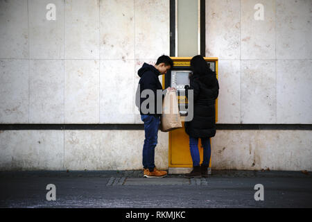 Frankfurt, Germany - January 05, 2017: Two young Asian tourists are standing at Frankfurt airport at a stamp vending machine on January 05, 2017 in Fr - Stock Photo
