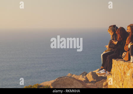 Sintra, Portugal - 01/05/19: People standing at edge of europe sunset, Cape roca. Westernmost European place. People hanging on a huge cliff - Stock Photo