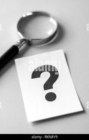 Magnifying glass on grey surface, next to big black question mark printed on white sheet of paper. Search for answers concept - Stock Photo