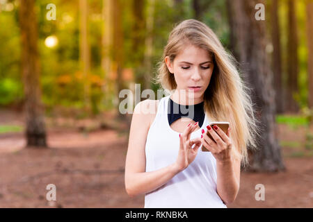 Beautiful blond young woman in park at sunset checking messages on her cellphone - Image - Stock Photo