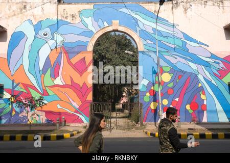 A couple walk past a street mural of a Oriental Pied Hornbill by Renato Reno in Lodhi Colony, New Delhi, India - Stock Photo