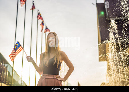 Young woman travels in Malaysia. Holds the Malaysian flag