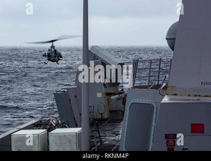 MEDITERRANEAN SEA, Jan. 29, 2019 - An AH-1W Super Cobra attack helicopter with the 22nd Marine Expeditionary Unit, lands on the flight deck of the San Antonio-class amphibious transport dock ship USS Arlington (LPD 24), Jan. 29, 2019. The USS Arlington is making a scheduled deployment as part of the 22nd MEU and the Kearsarge Amphibious Ready Group, in support of maritime security operations, crisis response and theatre security cooperation, while also providing a forward Naval and Marine presence. (U.S. Marine Corps photo by Staff Sgt. Andrew Ochoa/Released) - Stock Photo