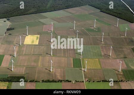 Aerial view of a windfarm and wind turbines in the middle of agricultural farmland with green fields, forest and a highway passing, Lower Saxonia, - Stock Photo