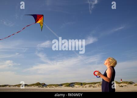 Young caucasian woman with kite at the beach and a lighthouse in the background, Amrum, Northfrisian, Schleswig-Holstein, Germany, Europe. - Stock Photo