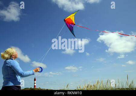 Young caucasian woman with kite and a lighthouse in the background, Amrum, Northfrisian, Schleswig-Holstein, Germany, Europe. - Stock Photo