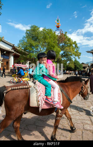 Pony rides around the Sideng market square in Shaxi, an former trading town for caravans plying the Tea Horse Trail in Jianchuan County,  Yunnan provi - Stock Photo