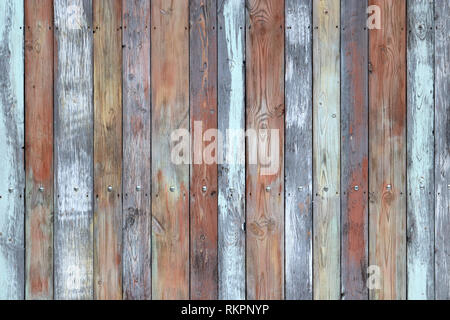 Old painted wood wall, multicolored wooden boards. Weathered panels texture with nails and knots for background - Stock Photo